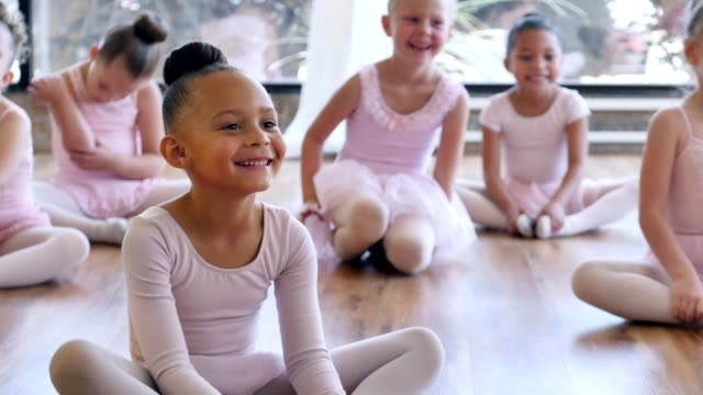 Adorable preschoolers at daycare laugh while warming up for ballet.